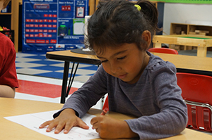 A student in CESJDS Gurim Junior Kindergarten practices handwriting